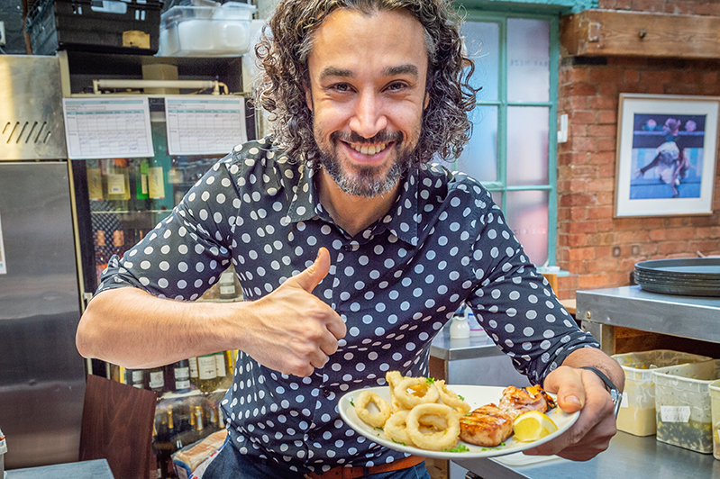 Restaurant owner giving thumbs up with plate of delicious foot