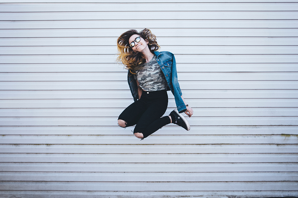 Girl in glasses jumping in the air being happy