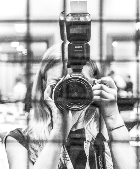 Carol Moir behind her canon camera with flash, lens facing
