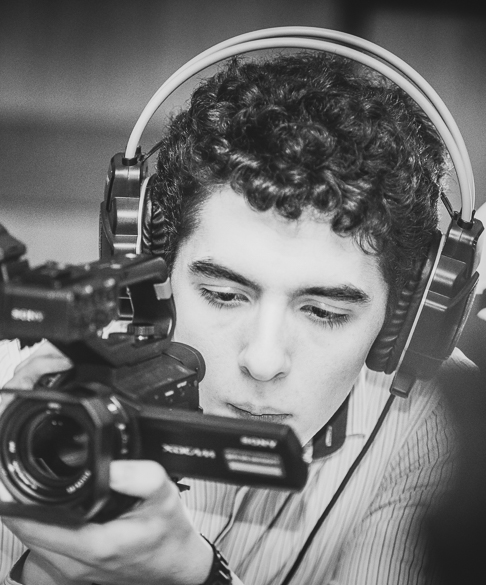 Michael Hailey with headphones on looking at the back of a film camera