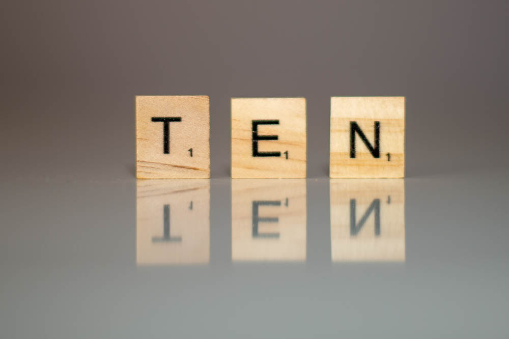 Scrabble letters, standing up on a surface, spelling out the word ten.