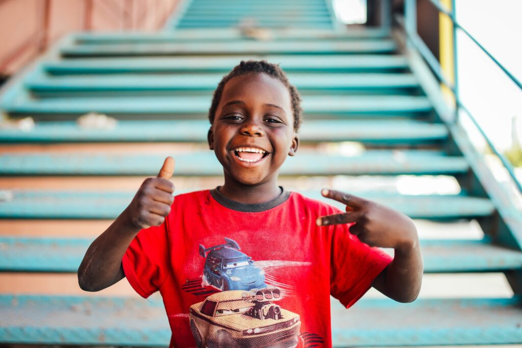 child with a red t-shirt grinning with their right hand showing thumbs up